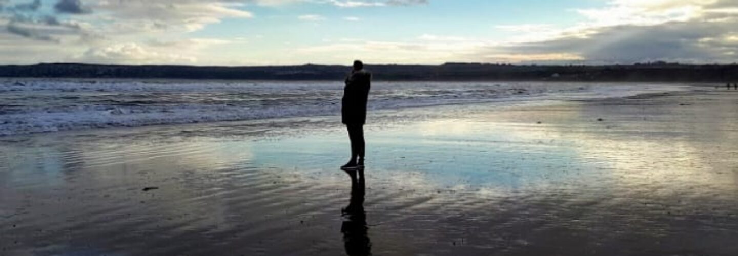 Charlie standing alone on a beach
